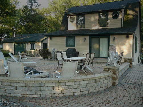 Extended summer living area with paver brick patio and large firepit in Lake Geneva