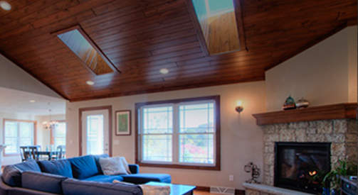 Cathedral wood ceiling with skylights and cozy fireplace for Lake Geneva home